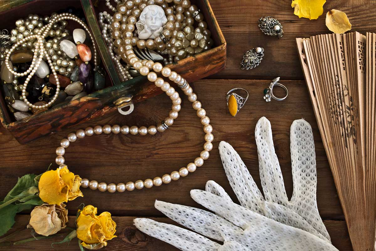 items scattered on wooden surface - pearls, rings, gloves and flower