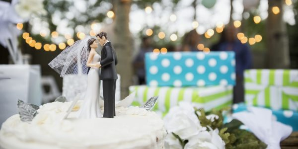 Bride and groom cake topper on a cake surrounded by gifts