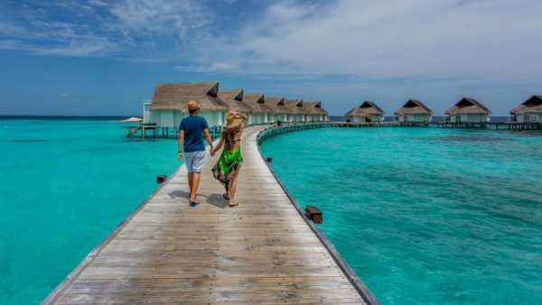 a man and woman tourist walking towards cottages