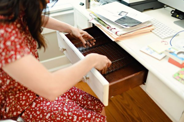 a woman in a vibrant red dress organizing her home office drawer