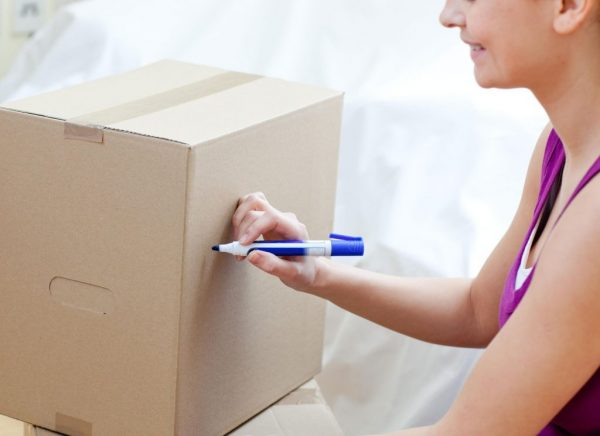 a woman writing on a cardboard box to label it for a move