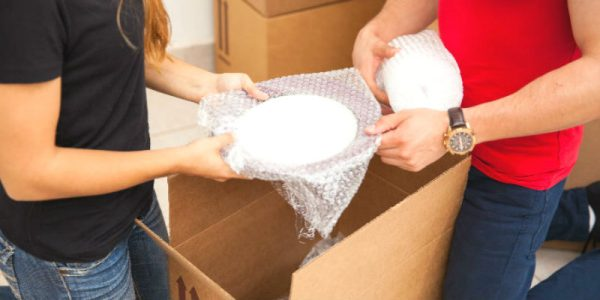 a couple putting plates inside bubble wrap for moving
