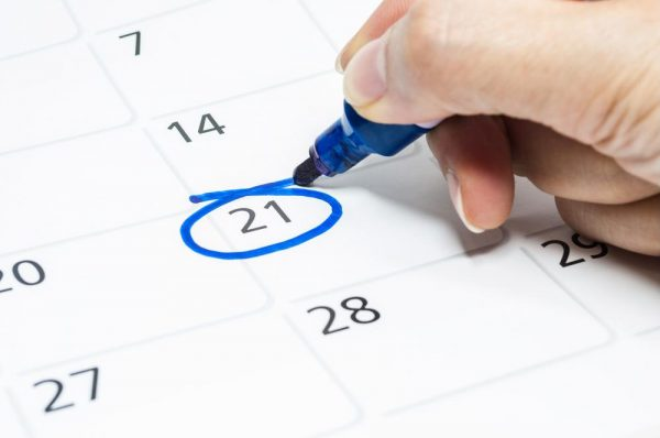 a person circling a date on the calendar with a blue marker