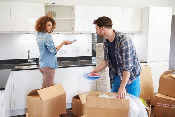 Couple Moving Into New Home And Unpacking Boxes Smiling At Each Other