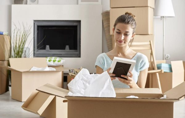 a woman looking at a picture frame while packing for a move