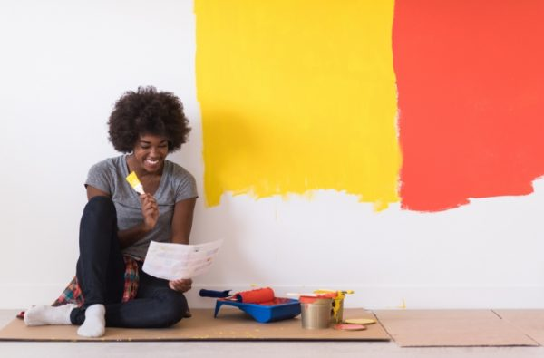 a black afro woman choosing which paint to color her walls