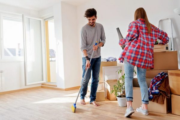 a young couple spring cleaning while the man is sweeping the floor