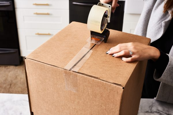 a woman sealing a cardboard box with packing tape