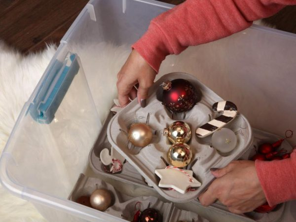 A woman organising christmas ornaments in a plastic box
