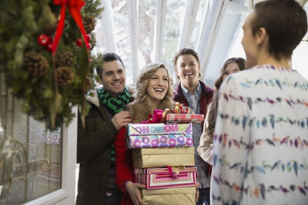 A woman holding a stack of gifts while being surrounded by her friends