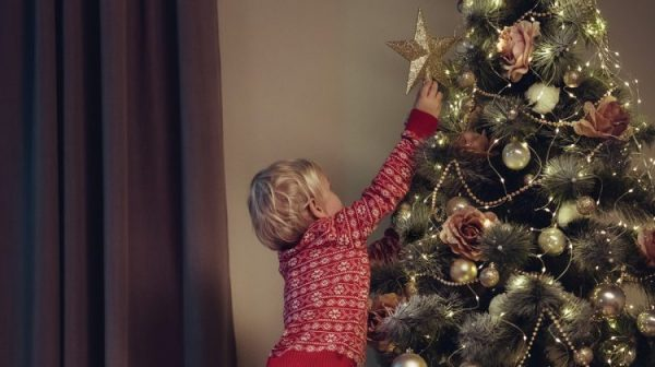 A baby decorating a christmas tree with a star ornament