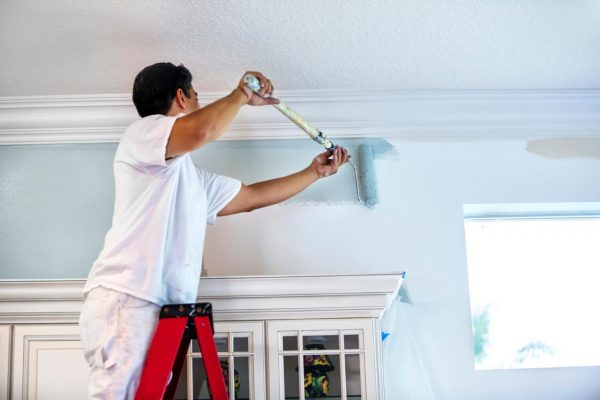 A man using a long paintroller to paint the walls